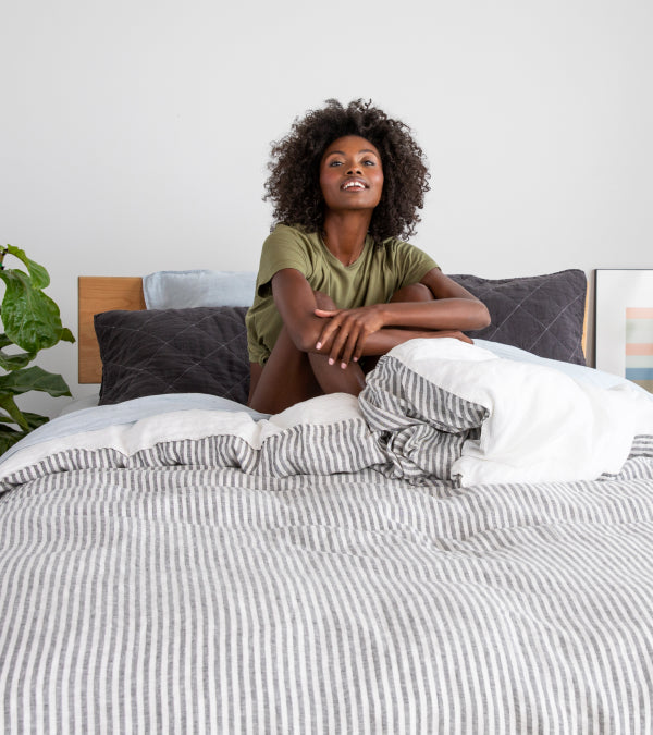 Woman in sage loungewear on a bed made up in linen sheets
