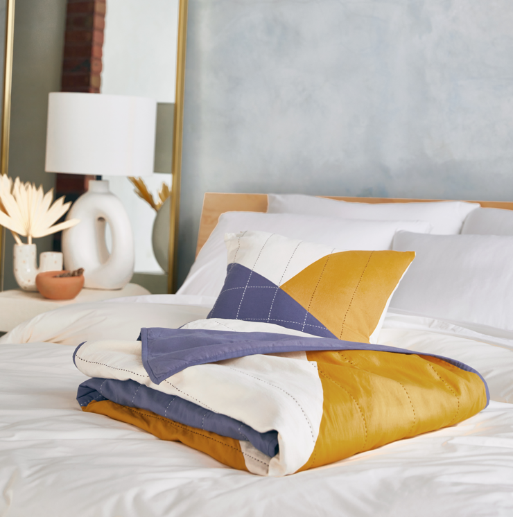 An Anchal Decorative Throw folded neatly atop crisp white sheets.