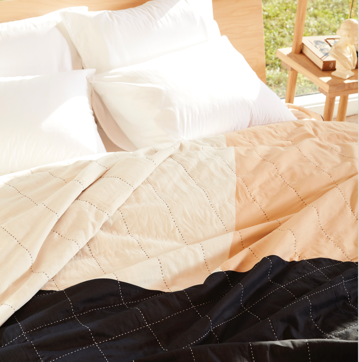 The Anchal Patchwork Quilt spread sumptuously over a bed, bathed in warm sunlight.