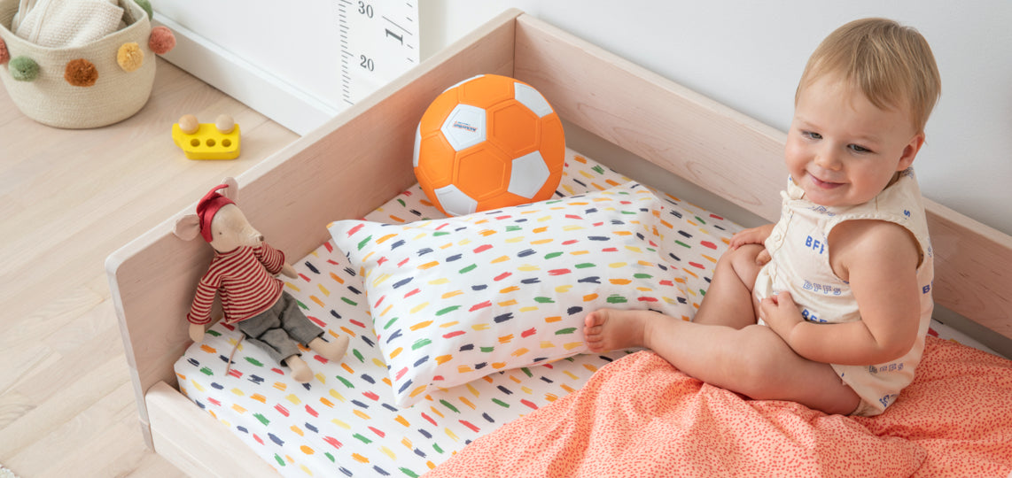 A baby gets ready to play on a bed made with a Blush Baby Bundle.