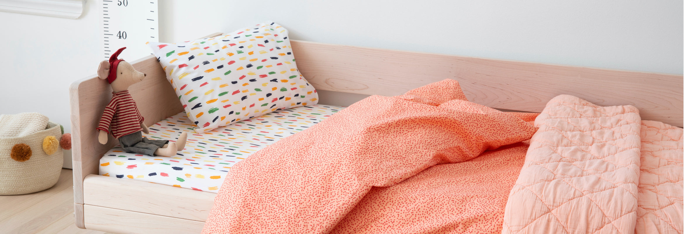 A bed made with blush sheets.