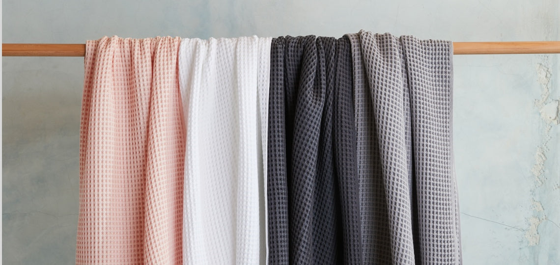 All four colors of our Waffle Towels spread across a wooden towel rack, drying quickly.