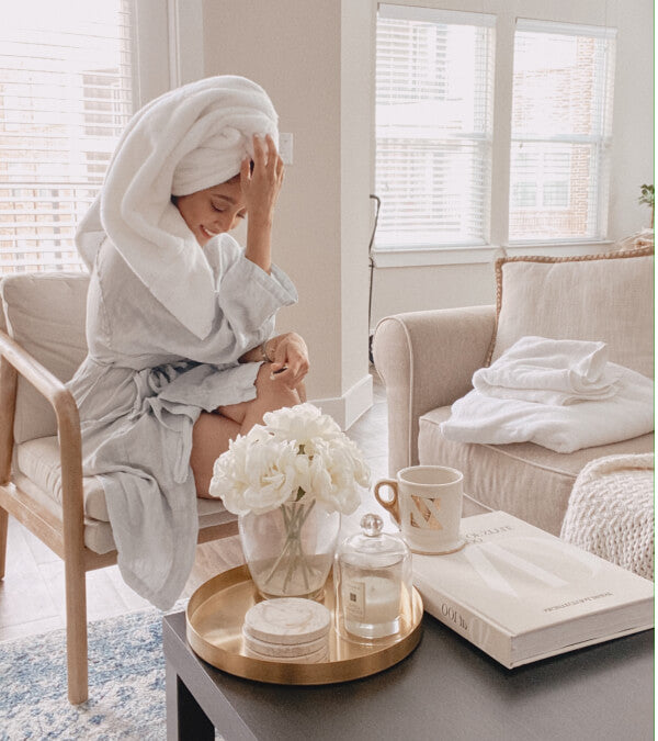 Woman in an all white room in a white linen robe, with her hair twisted up in a white towel, drying.