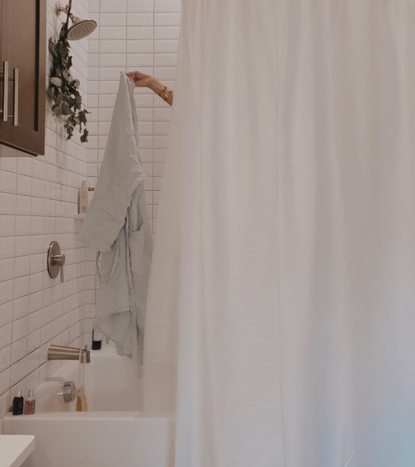 White bathroom with a white shower curtain.  An arm reaches out from the shower holding a white linen robe.