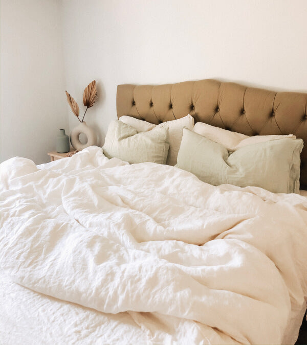 Bed made up in rumpled cream linen sheets.  Everything in the room is beige.
