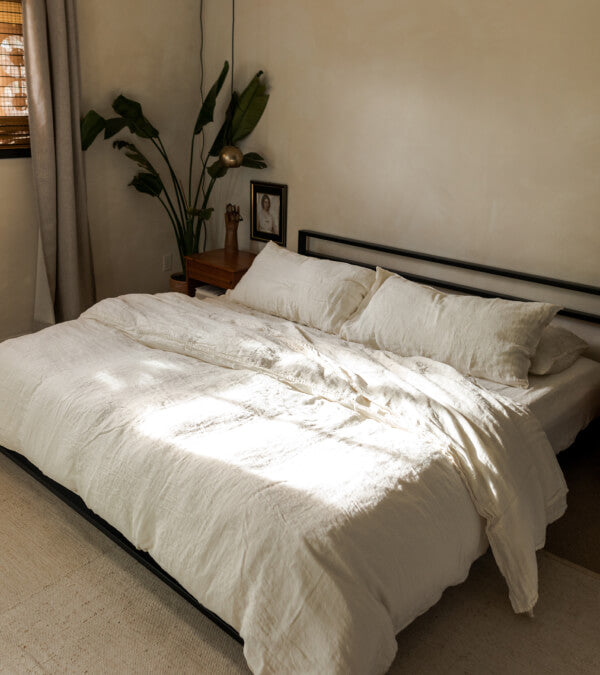 Bed made up in rumpled cream linen sheets.  Everything in the room is beige. Big palm plant in the background