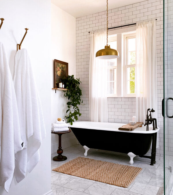 All white bathroom with a black clawfoot tub with white towels