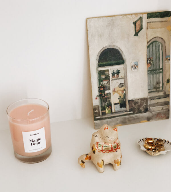 Magic Hour candle on a shelf with a lucky cat
