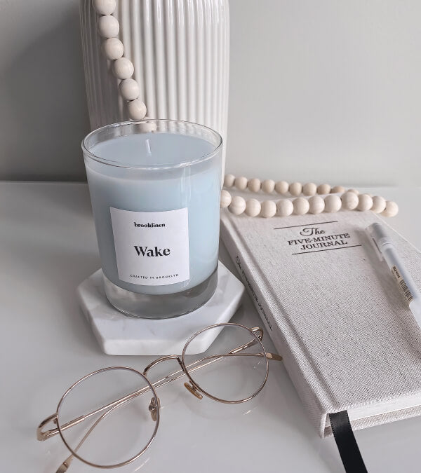 Wake candle next to a pair of glasses and a journal