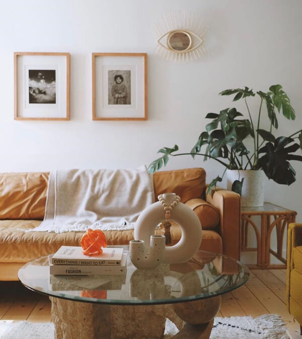 Living room with a cognac leather sofa, a grey wool throw blanket, and a big palm plant