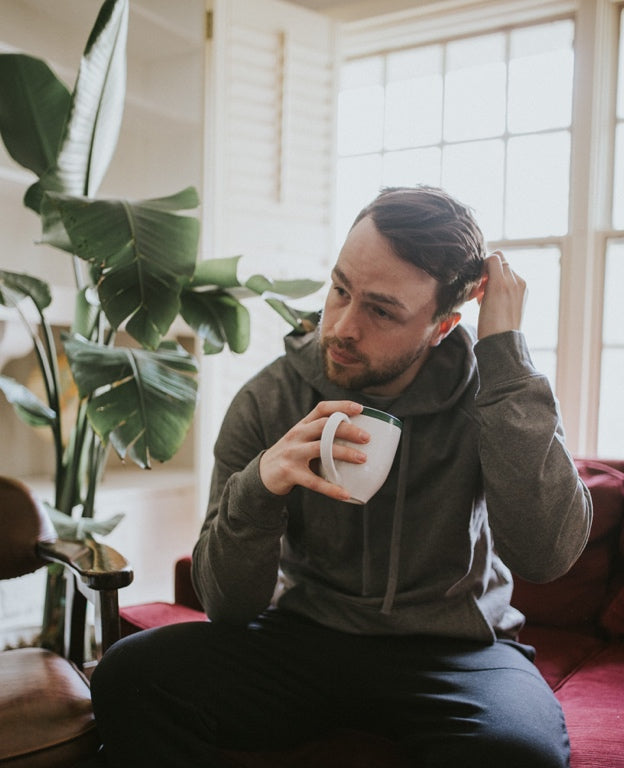 A man wearing loungewear enjoys a cup of coffee.