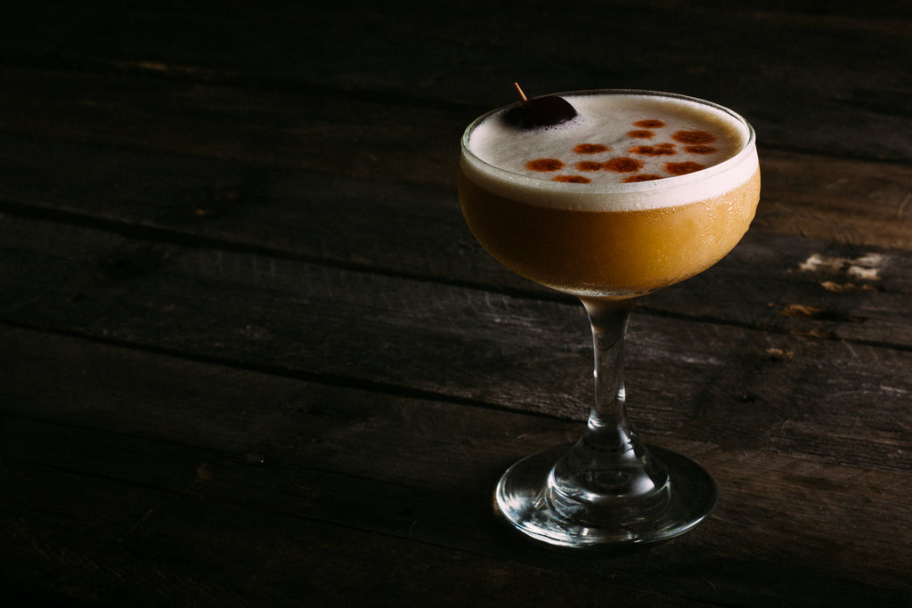 Delicious whiskey sour with conifer simple syrup, egg white, bitters and maraschino cherry