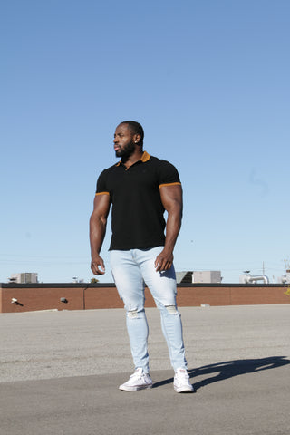 man in polo shirt and tapered ripped jeans with a blue sky