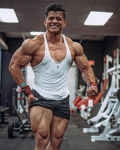 aesthetic bodybuilder wearing tank top and shorts in gym