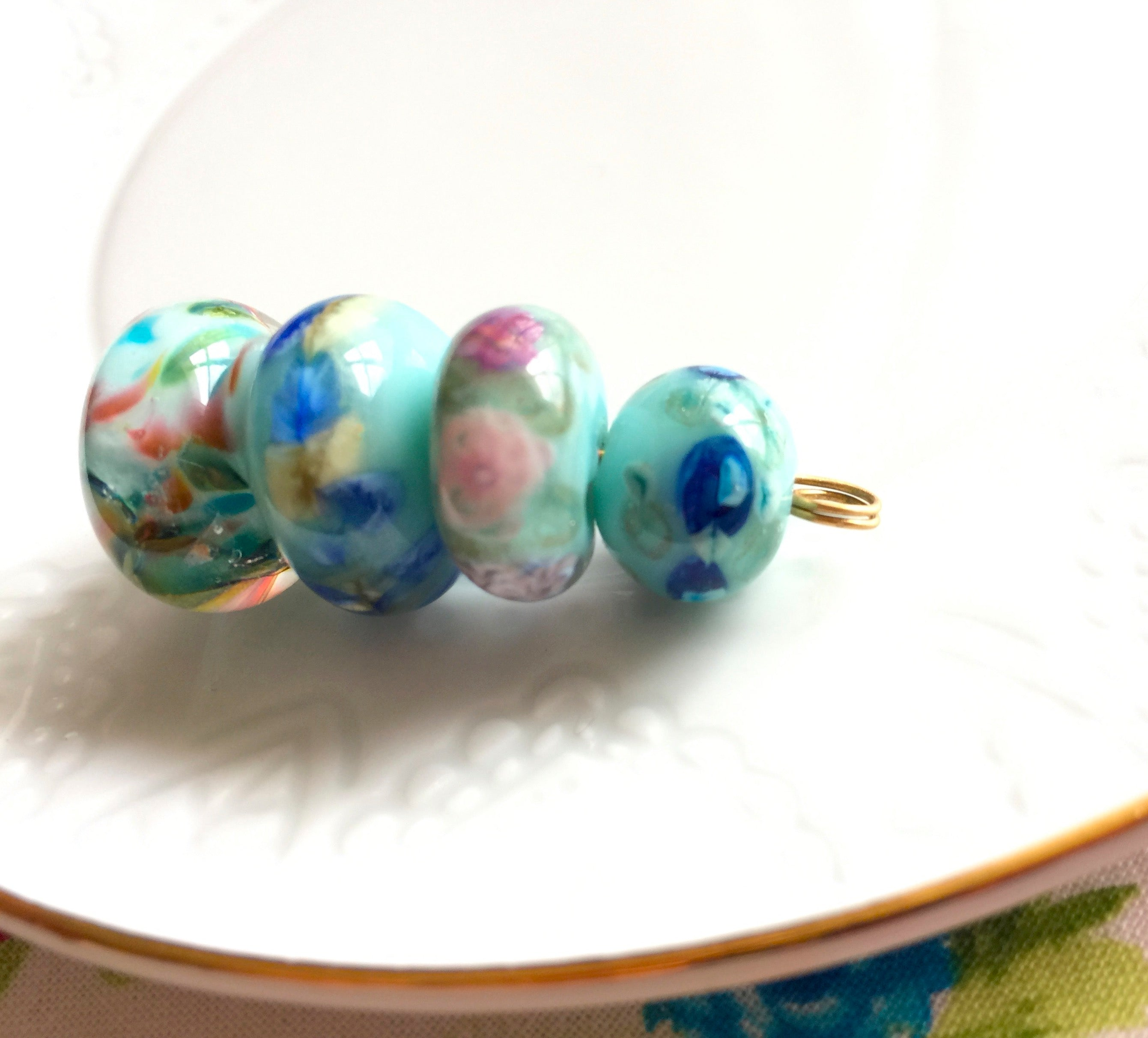 Set of 4 Handcrafted Lampwork Glass Beads in pretty light aqua blue with colorful spots, swirls, and floral embellishments.