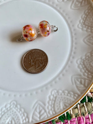 Set of 2  spotted lampwork beads in soft pink with orange, pink, and mint speckles.