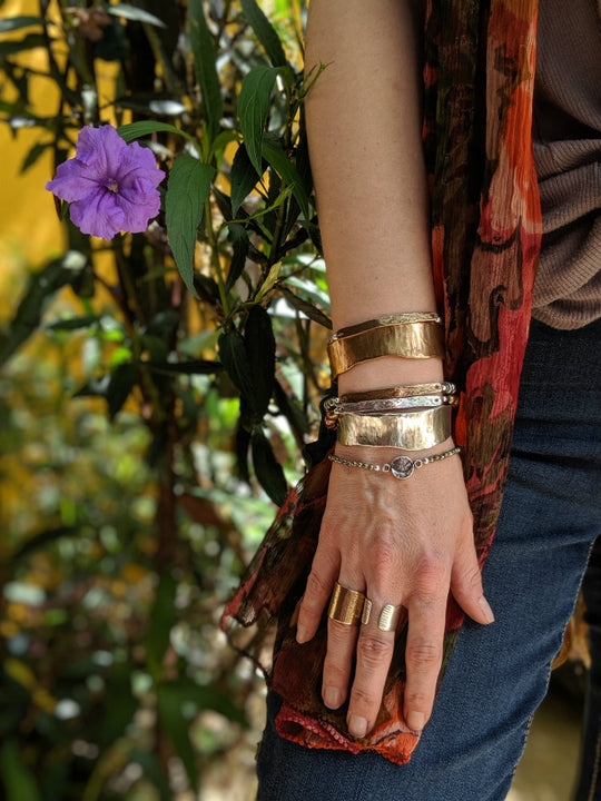 rings and bracelets on a hand with a purple flower