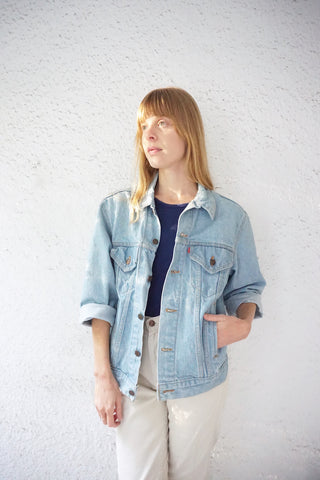 young woman wearing levi's jean jacket in the sunlight