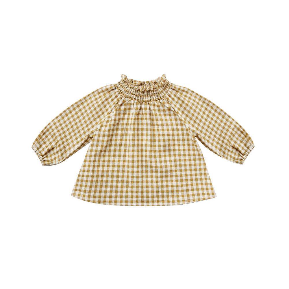 This Audrey blouse features a smocked mock neck, elastic sleeve openings and loose blousy fit.  Color: goldenrod gingham  Care: Machine wash cold. Tumble Dry low. Minor shrinkage may occur if tumble dried.  Made of 55% linen, 45% cotton