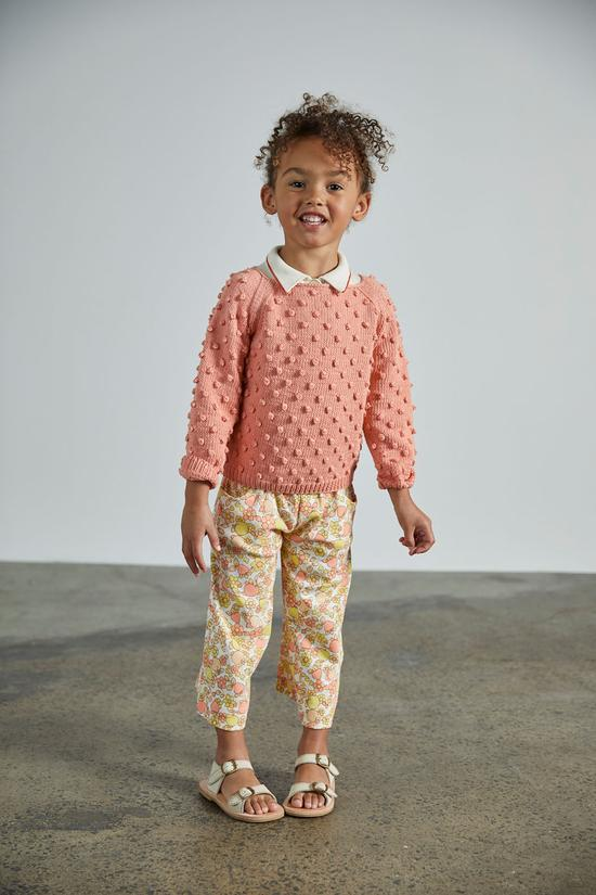 Misha & Puff signature hand knit style with an all over popcorn stitch. One of their collectabel pieces loved by all. A classic raglan sleeve detail with a natural corozo button closure at the back neck.