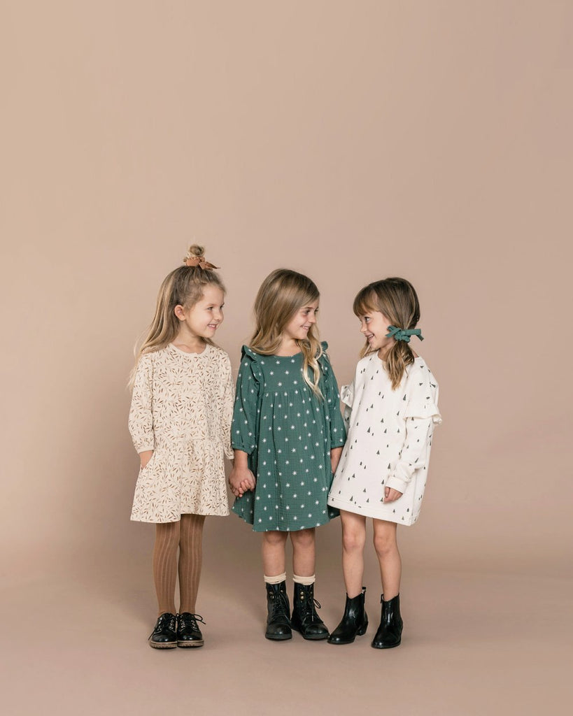 Rylee + Cru sweatshirt dress with an all over evergreen tree print that's lined in a warm fleece. Green Star dress with the all over star print in white. Pair with wheat socks or tights to complete the look.