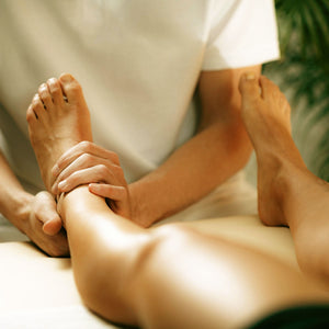 osteopath massaging leg for pain relief