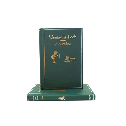 Book is hunter green with title and detailing in gold foil. Illustration of Christopher Robin pointing at Pooh and Pooh on the floor.