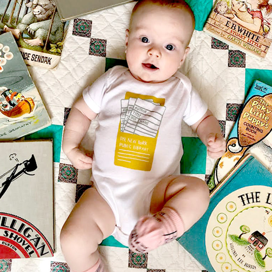 All white baby onesie. The item features an image of the NYPL Library Cards in a yellow pocket.