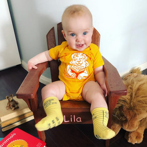 Orange onesie with illustration of a lion reading a book in the front.