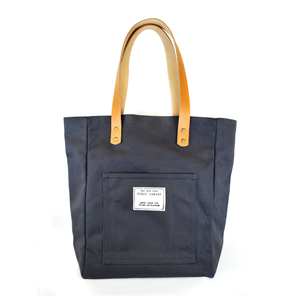 "White background, rectangular shaped stamp on the outside pocket. Text on stamp reads ""The New York Public Library. Astor, Lenox and Tilden Foundation.""  Tote has leather handles."