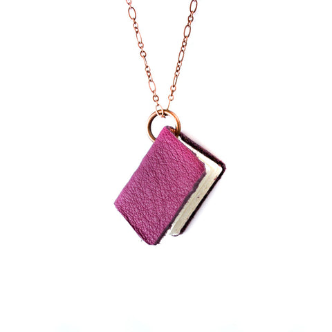 Purple miniature book on cooper chain. Paper inside the book is blank.