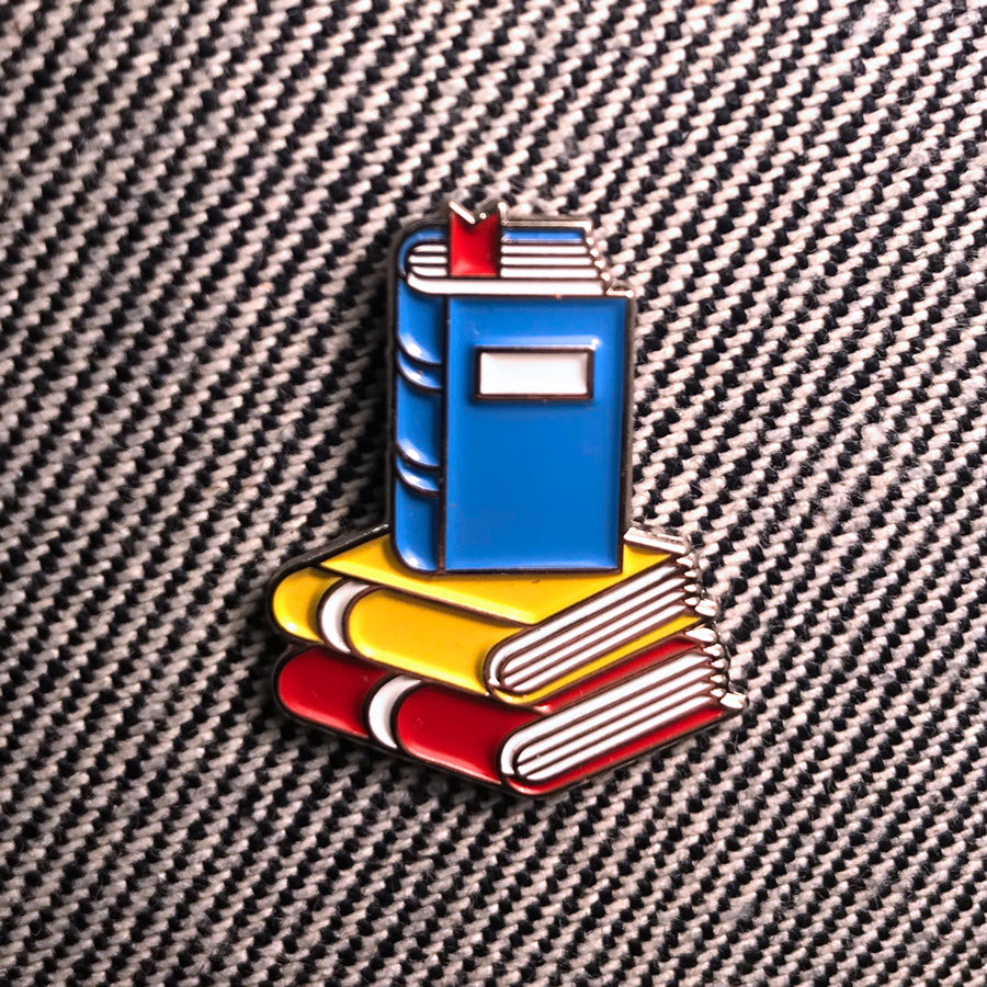 Pin features 3 books (red, yellow and blue) in different positions. No text on pin.