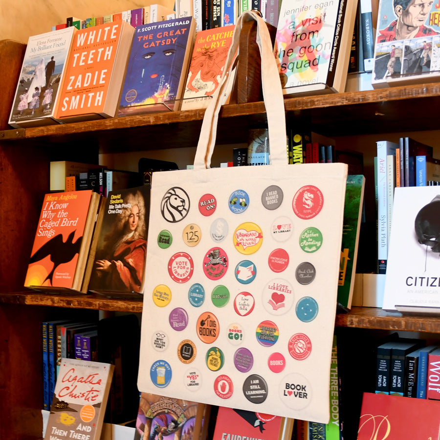 Tote covered with colorful illustrations of buttons related to reading, libraries and books hanging from a book cart.