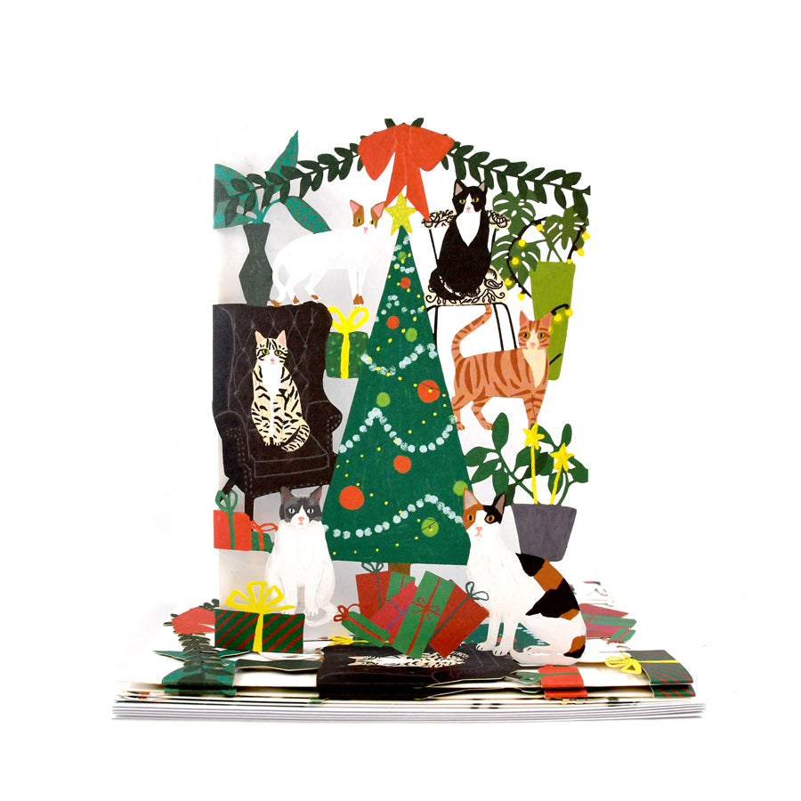 Laser cu-put card with different types of cats in different positions around a Christmas tree and gifts.