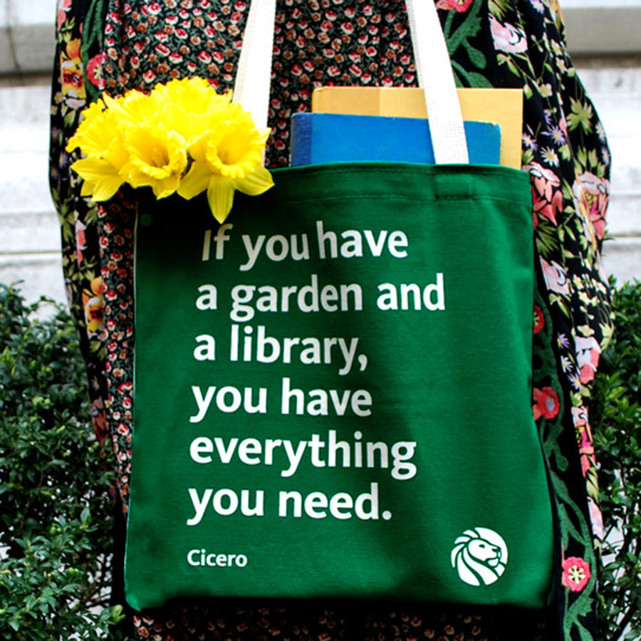 Quote on green background tote bag with cream colored handles.