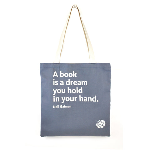 Quote on gray background tote bag with cream colored handles.