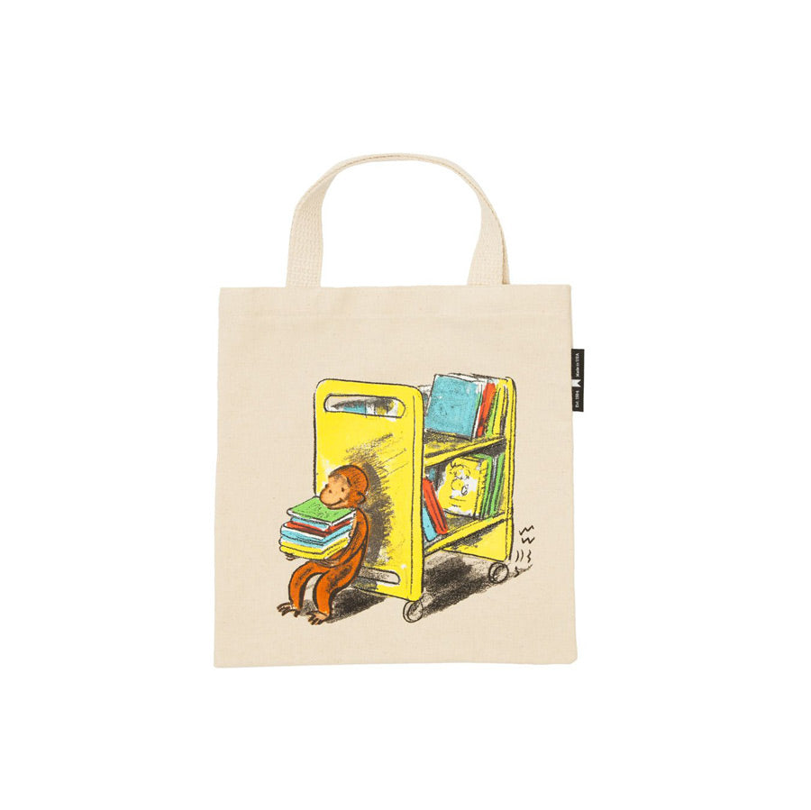 Illustration of curious George pushing a yellow book cart on a light beige background tote.