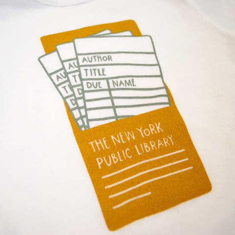 The NYPL Library card image on the baby onesie. The image is mustard yellow and white.