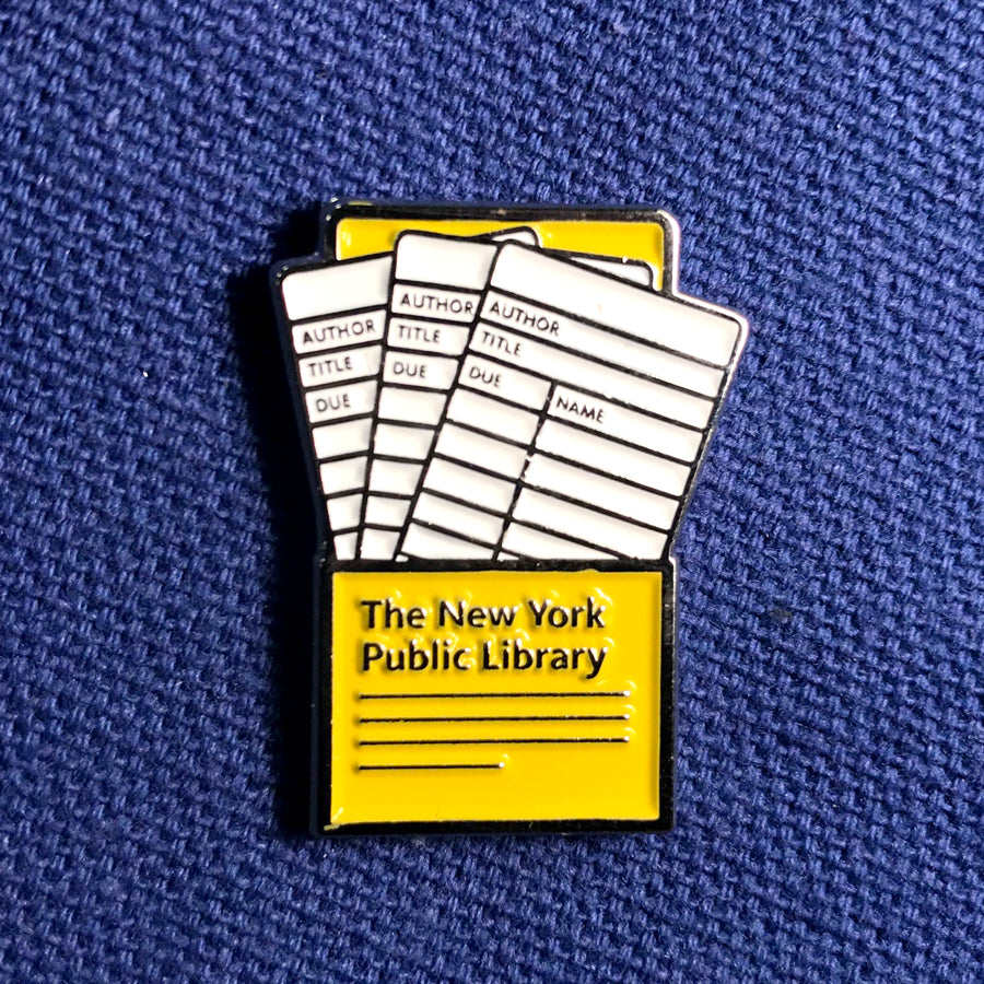 "Three white cards inside of a yellow pocket with text ""The New York Public Library"" at the bottom."