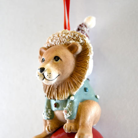 Lion is wearing a green-gray polka dotted sweater.