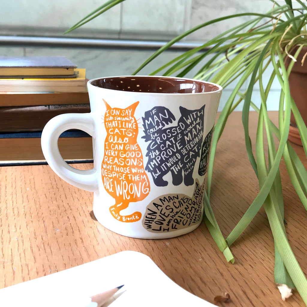 Mug has a white background with different shapes of cats in different colors.