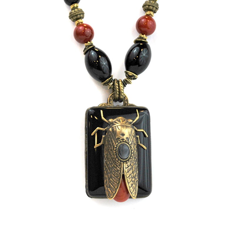Brass Locust on top of a rectangular shaped black onyx.