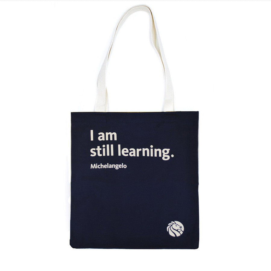 Quote on navy blue background tote bag with cream colored handles.
