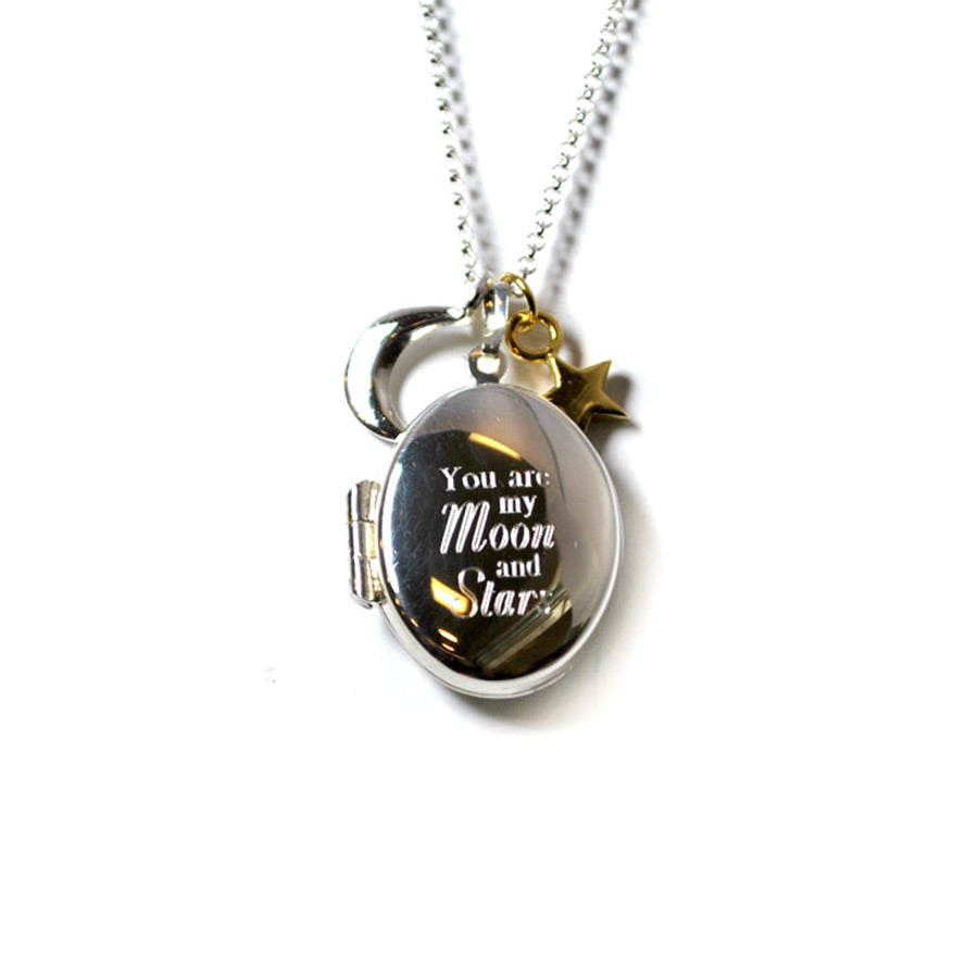 One silver moon charm and one gold plated star charm hanging on top of locket.