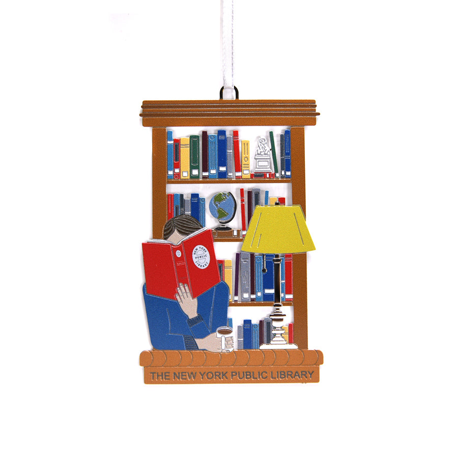 Colorful ornament features a person reading a red book with the oval vintage NYPL stamp on it. The ornament also features one of the lamps from the Rose Reading Room and in the background there is a shelf with books, a globe and our Lion Bookend.