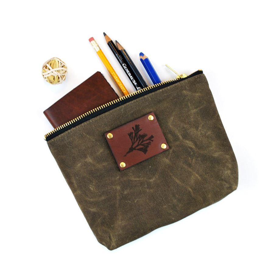 Pouch is a dark-olive green color. It has the illustration of an algae on leather-squared piece placed in the upper center area of the pouch.