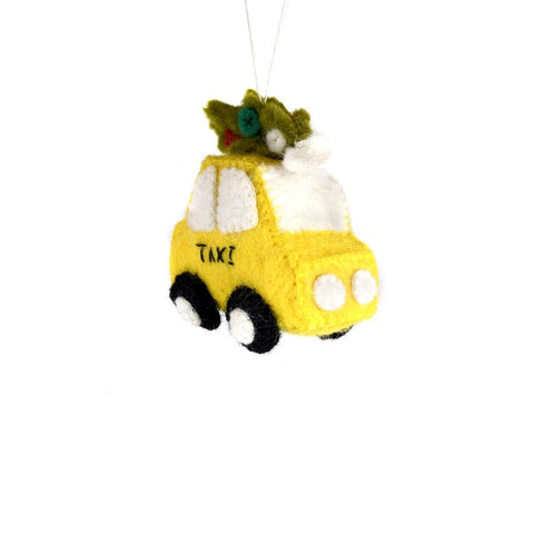 "Yellow taxi with Christmas tree on top. Text reads ""taxi"" on the door."