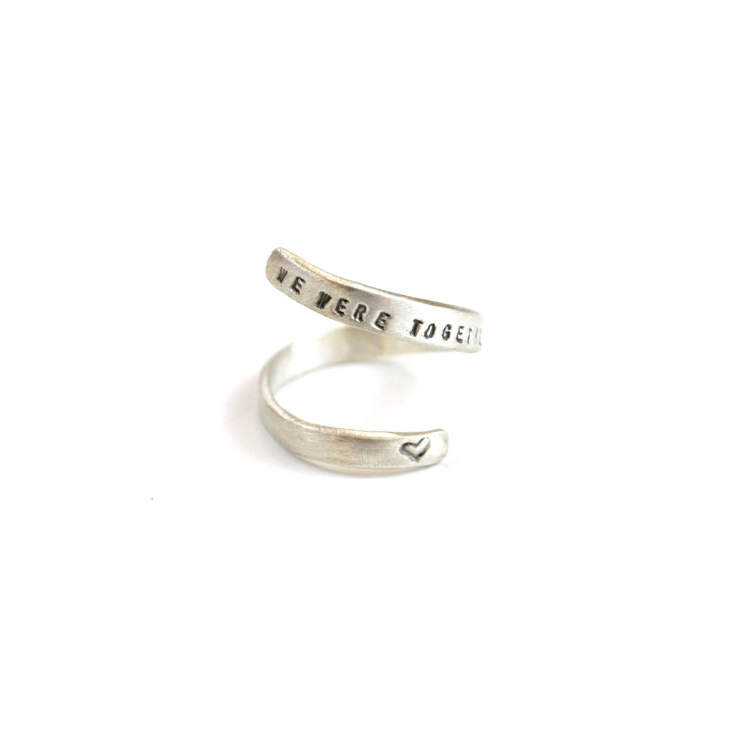 Wrap-around ring with quote on black on one end and a heart on the other end.