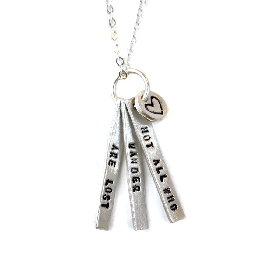 Necklace has three silver, thin, long pendants with quote in black.