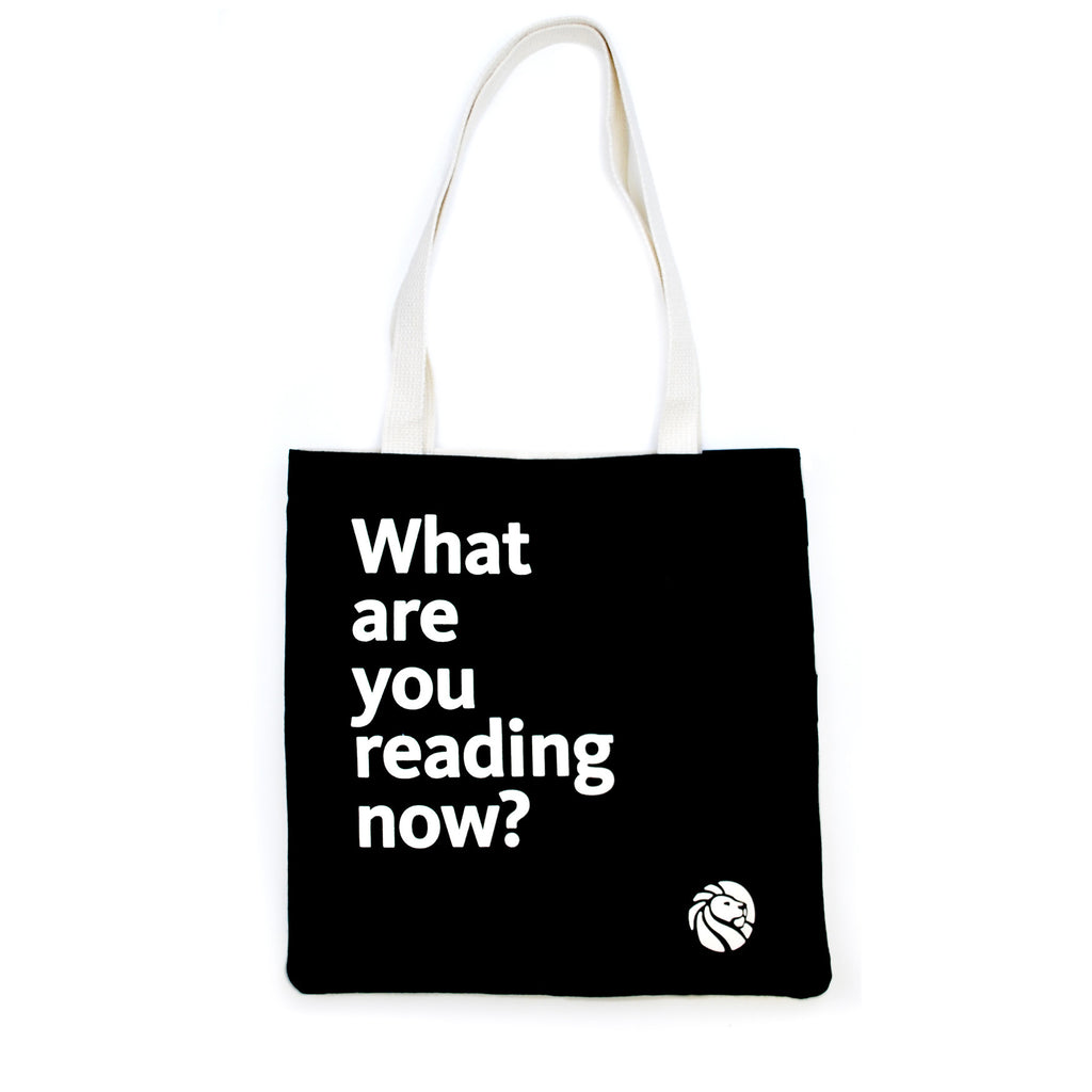 Quote on black background tote bag with cream colored handles.